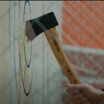 An axe hitting the bullseye in an axe throwing game