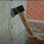 An axe hitting the bullseye in an axe throwing game